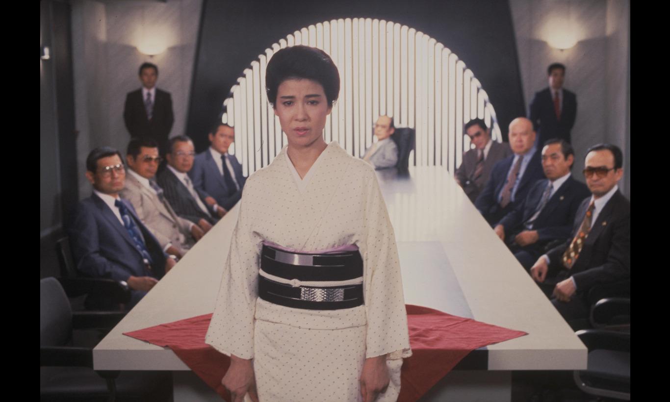 白い着物姿で強面の人達の前に立ち演技をする映画の中の十朱幸代
